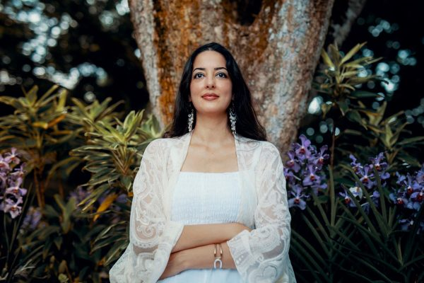 Zeeba Khan sitting in front of tree with tropical plants and flowers